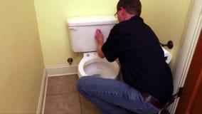 La mano del fontanero que repara el asiento de inodoro metrajes