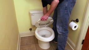 La mano del fontanero que repara el asiento de inodoro almacen de metraje de vídeo