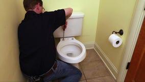 La mano del fontanero que repara el asiento de inodoro almacen de video