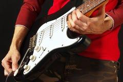 La mano del guitarrista de la roca inserta el conector de entrada a la guitarra eléctrica en fondo negro Foto de archivo libre de regalías
