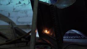 La mano del herrero en guantes protectores suelda un metal almacen de metraje de vídeo