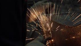 La mano del herrero en guantes protectores suelda un metal almacen de video