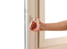La mano del hombre abre el plástico blanco la ventana Aislado en blanco imagen de archivo