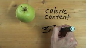 La mano del hombre anota el contenido calórico de la manzana en superficie de madera almacen de video