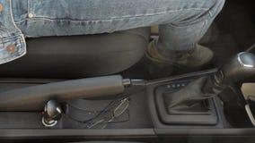 La mano del hombre arriba y abajo del freno de mano en el coche Día asoleado automóvil Gafas metrajes
