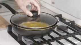La mano del hombre cierra la tapa de preparar los huevos revueltos con la salchicha en un sartén en estufa de gas almacen de video