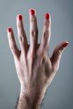 La mano del hombre con el esmalte de uñas rojo Imagen de archivo