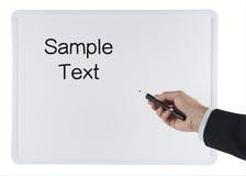 La mano del hombre con el marcador que señala a un tablero blanco Imagen de archivo libre de regalías