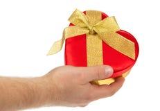 La mano del hombre con la caja de regalo de forma del corazón imágenes de archivo libres de regalías