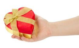 La mano del hombre con la caja de regalo roja un corazón fotografía de archivo