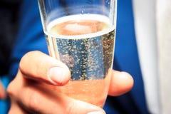 La mano del hombre con un vidrio de champán Foto de archivo libre de regalías