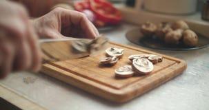 La mano del hombre cortó cuidadosamente setas salvajes en un tablero de madera de la cocina almacen de video