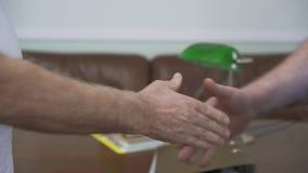 La mano del hombre da dólares al hombre irreconocible Dos hombres maduros mayores que sacuden las manos cerca para arriba Relació almacen de video