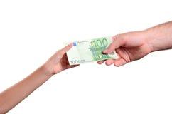 La mano del hombre da el euro de la cuenta 100 en la mano de un niño Foto de archivo libre de regalías