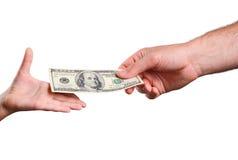 La mano del hombre da la cuenta 100 dólares de EE. UU. en la mano de un niño Fotos de archivo libres de regalías
