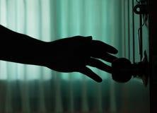 La mano del hombre de la sombra abre la puerta Imagenes de archivo