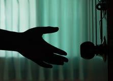 La mano del hombre de la sombra abre la puerta Foto de archivo