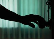 La mano del hombre de la sombra abre la puerta Imagen de archivo libre de regalías