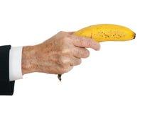 La mano del hombre de negocios con el plátano tiene gusto del arma, sobre blanco Imagen de archivo