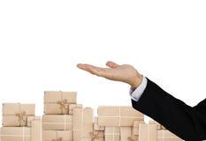 La mano del hombre de negocios con el servicio postal de paquetes encajona los fondos, aislados en el fondo blanco Imagen de archivo
