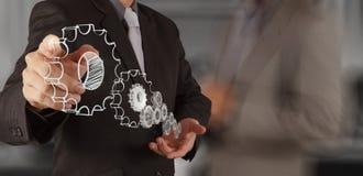 La mano del hombre de negocios dibuja el engranaje al éxito Imagen de archivo libre de regalías