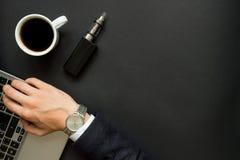 La mano del hombre de negocios en el ordenador portátil y el cigarrillo electrónico Imagen de archivo
