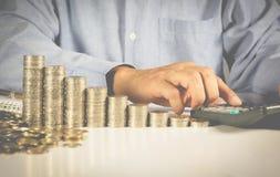 La mano del hombre de negocios está presionando la calculadora con las monedas de la pila Imagenes de archivo