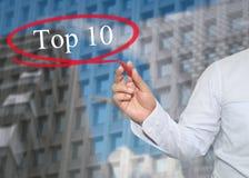 La mano del hombre de negocios joven escribe el top 10 de la palabra en rascacielos Fotos de archivo libres de regalías