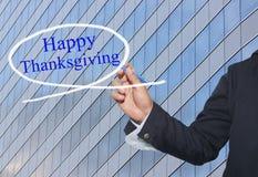 La mano del hombre de negocios joven escribe a palabra acción de gracias feliz en s Imágenes de archivo libres de regalías