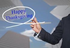 La mano del hombre de negocios joven escribe a palabra acción de gracias feliz en s Foto de archivo libre de regalías