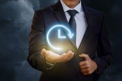 La mano del hombre de negocios lleva a cabo el icono de horas con la flecha Imagen de archivo libre de regalías