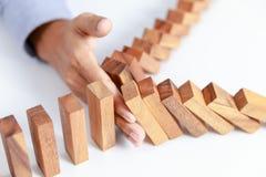 La mano del hombre de negocios protege el bloque de madera del juguete contra peligro y cae imagen de archivo libre de regalías