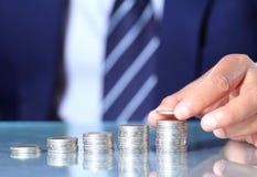 La mano del hombre de negocios puso monedas Foto de archivo libre de regalías