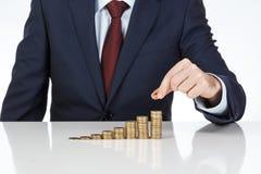 La mano del hombre de negocios que apila un euro acuña en columnas cada vez mayores Foto de archivo libre de regalías