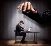 La mano del hombre de negocios que controla una marioneta del trabajador Foto de archivo