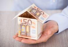 La mano del hombre de negocios que sostiene la casa hecha de notas euro Fotos de archivo libres de regalías