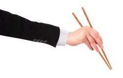 La mano del hombre de negocios que sostiene los palillos fotografía de archivo libre de regalías