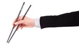 La mano del hombre de negocios que sostiene los palillos foto de archivo