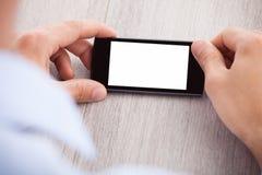 La mano del hombre de negocios que sostiene smartphone con la pantalla en blanco Imágenes de archivo libres de regalías