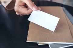 La mano del hombre de negocios que sostiene y que da la tarjeta de visita vacía con los cuadernos en la tabla fotos de archivo libres de regalías
