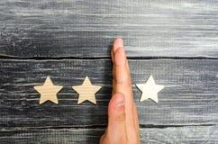 La mano del hombre de negocios separa la tercera estrella de los otros cuatro pérdida de la tercera estrella, la caída en el grad imagen de archivo libre de regalías
