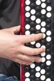 La mano del hombre en el teclado del acordeón Foto de archivo