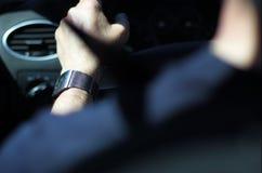 La mano del hombre en el volante Fotografía de archivo