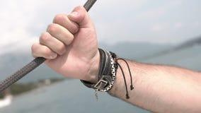 La mano del hombre en las pulseras de cuero se sostiene sobre cuerda del mar del barco móvil metrajes