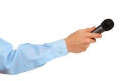 La mano del hombre en una camisa azul que sostiene un micrófono Imágenes de archivo libres de regalías