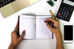 La mano del hombre está escribiendo en el escritorio Escritorio de oficina blanco con smartpho Fotografía de archivo