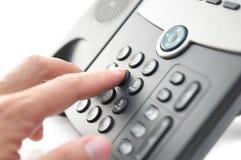 La mano del hombre está marcando un número de teléfono con cogidas las auriculares Imagen de archivo libre de regalías