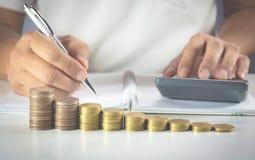 La mano del hombre está presionando la calculadora con las monedas de la pila Imágenes de archivo libres de regalías