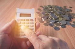 La mano del hombre está presionando la calculadora con las monedas en la tabla Foto de archivo