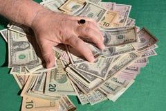 La mano del hombre exprime billetes de dólar imagenes de archivo